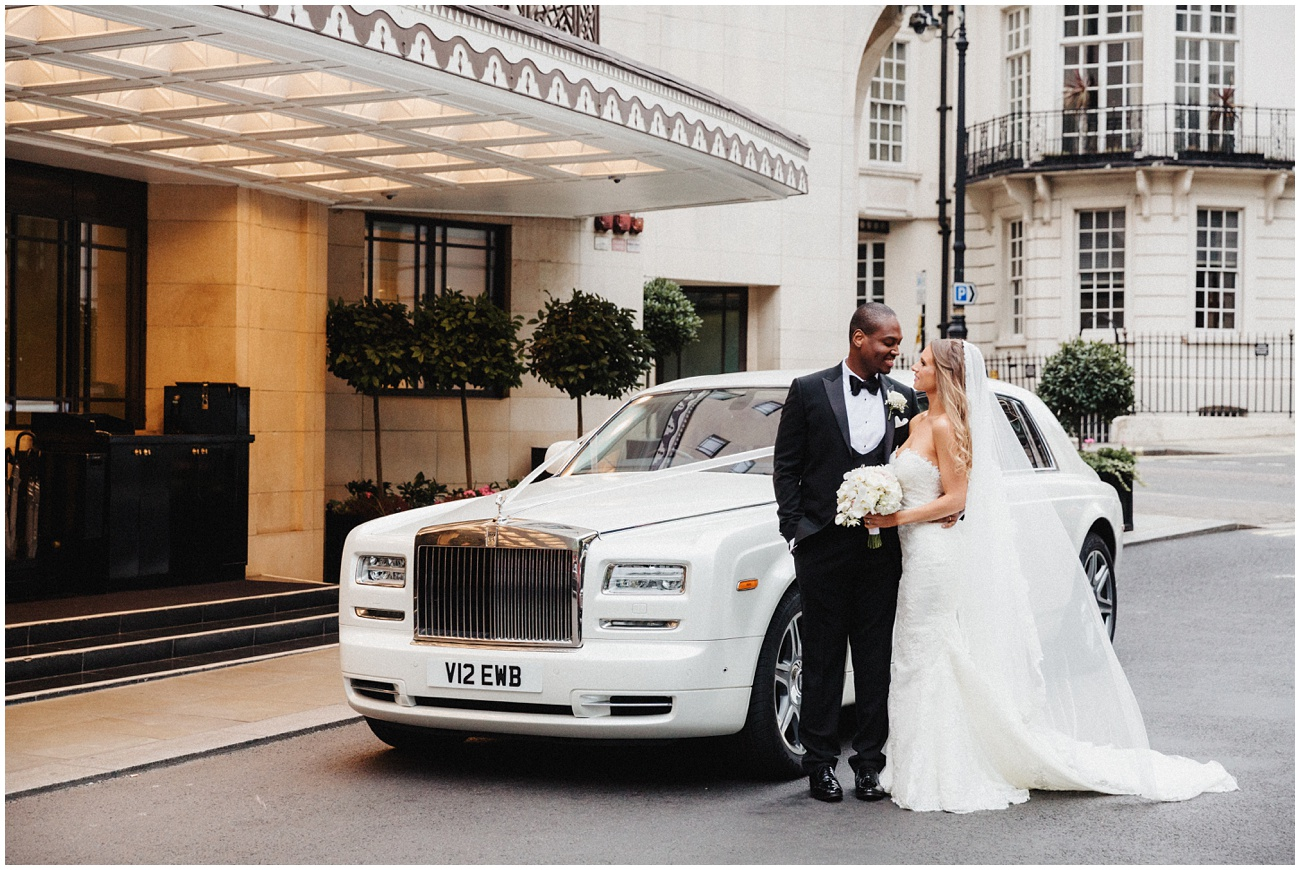 The bride and groom look at each other and pose by their wedding car outside the Dorchester Hotel in London