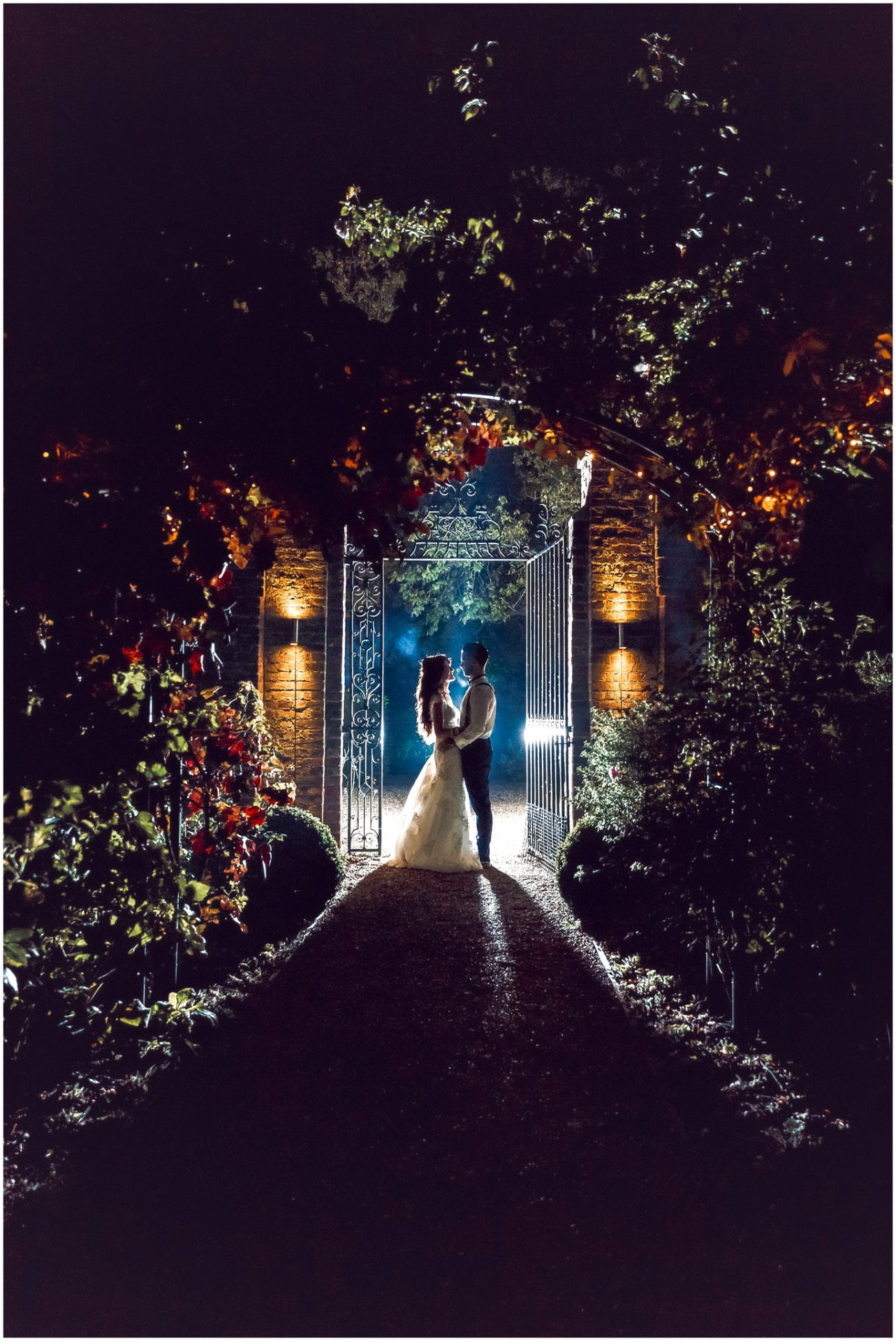Bride-and-Groom-holding-each-other-at-night-in-the-gardens-of-Braxted-Park