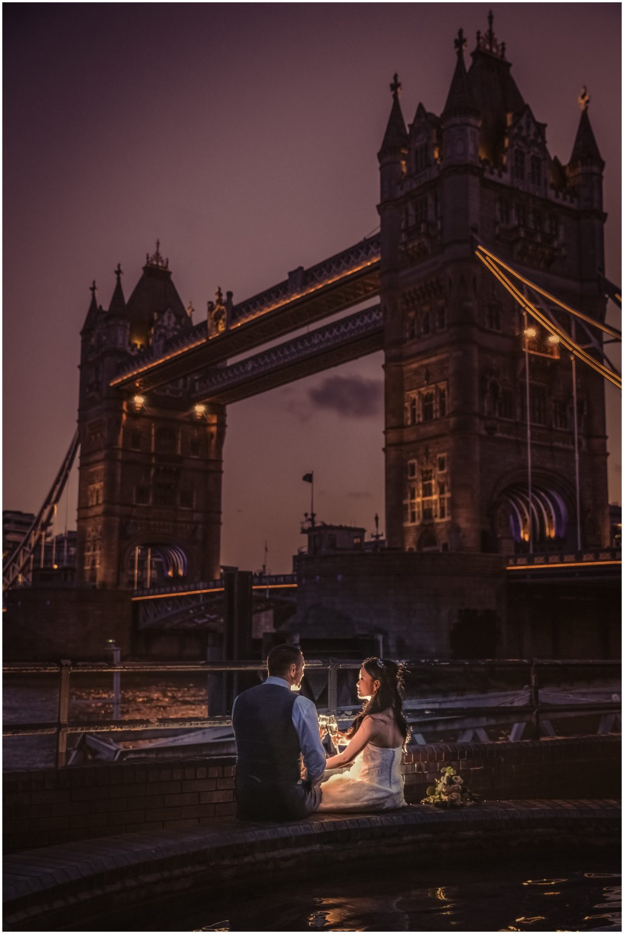 Evening-shot-of-bride-and-groom-drinking-champagne-near-tower-bridge-London