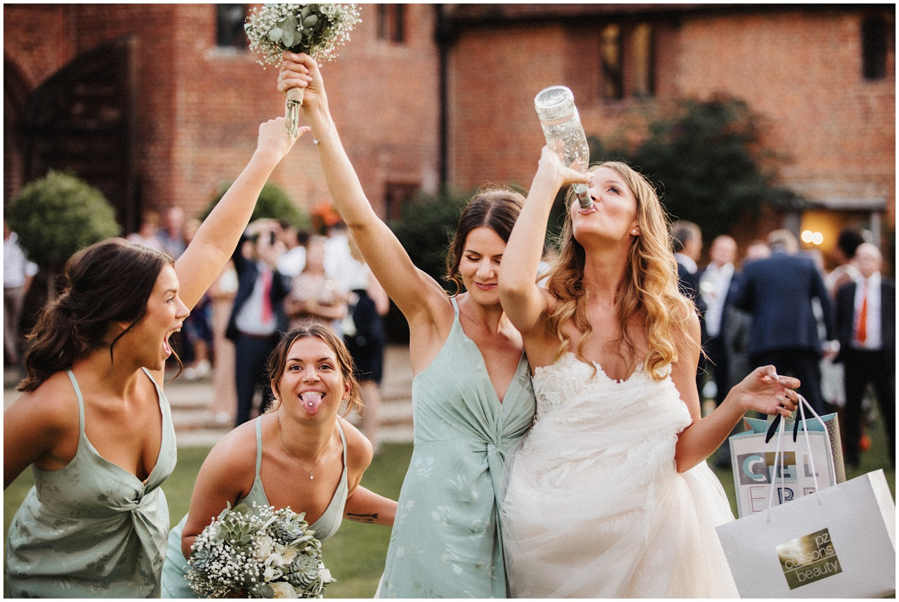 Bride and her bridesmaids enjoy a drink and laugh in the gardens at Leez Priory
