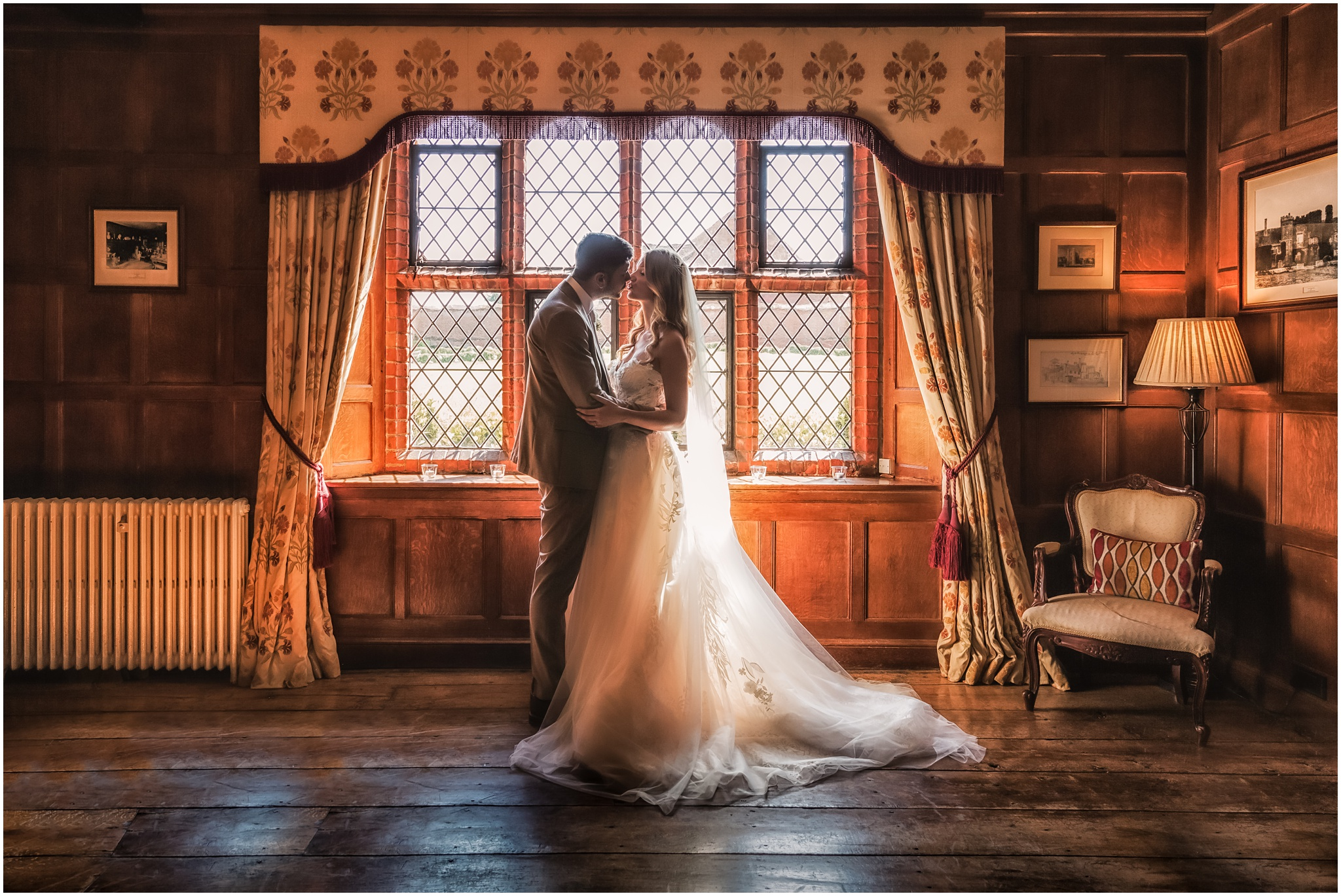 Bride and groom kiss in the piano room at Leez Priory