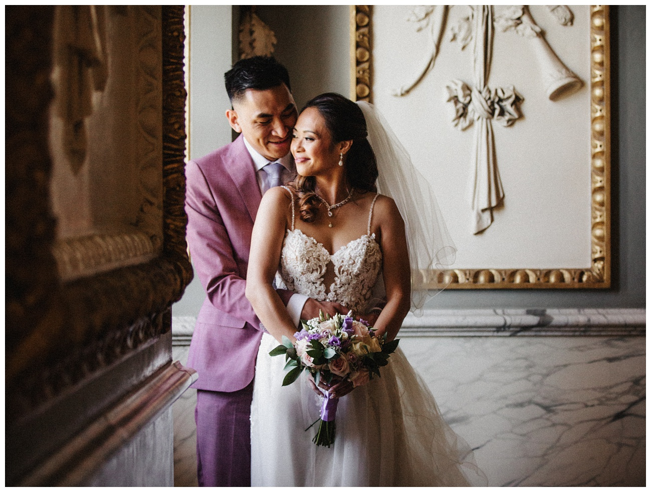 The smiling groom holds the happy bride by a window at Moor Park Mansion