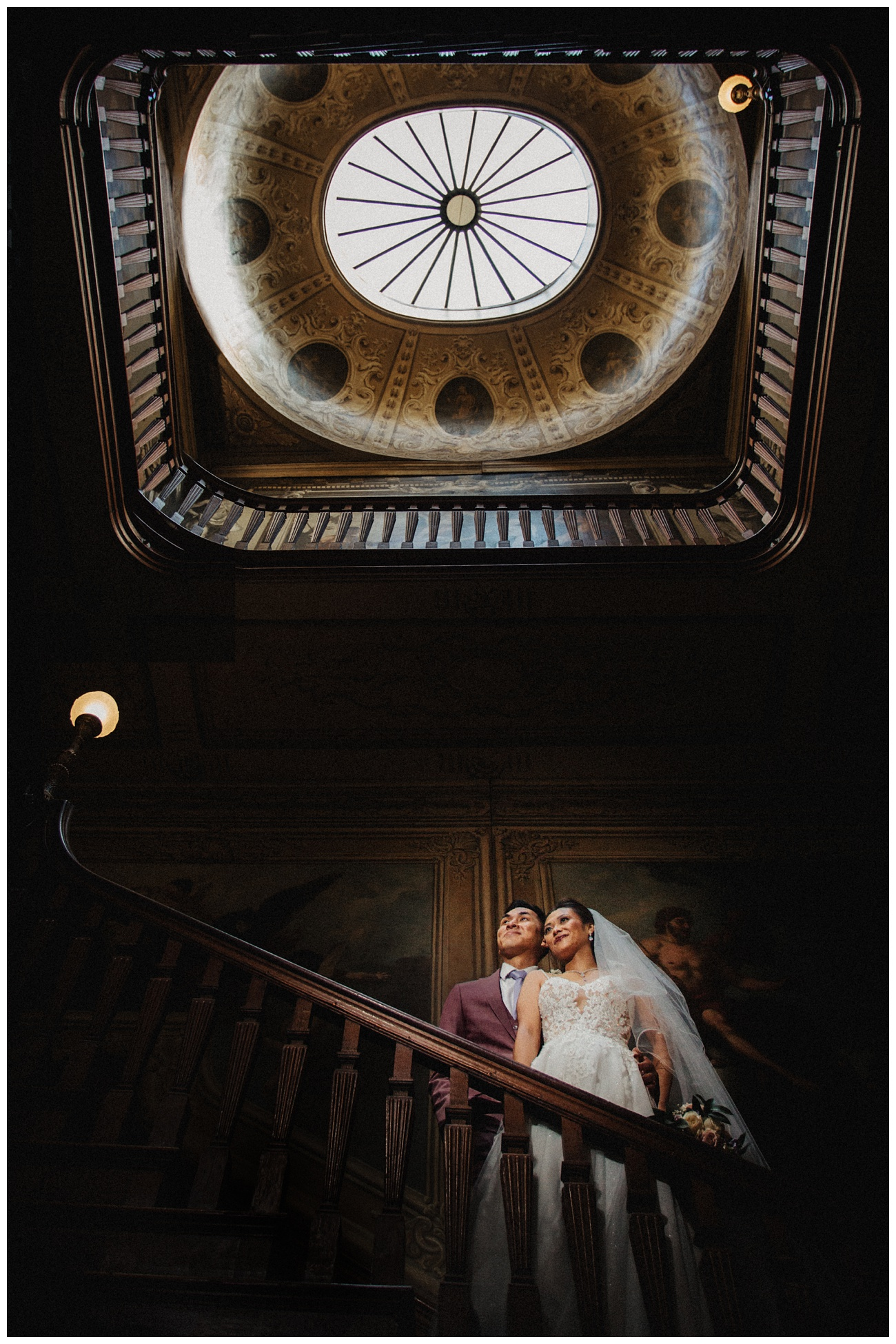 The bride and groom on the staircase at Moor Park Mansion