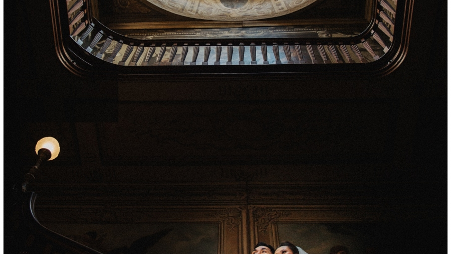 Bride and groom pose on the staircase inside Moor Park Mansion