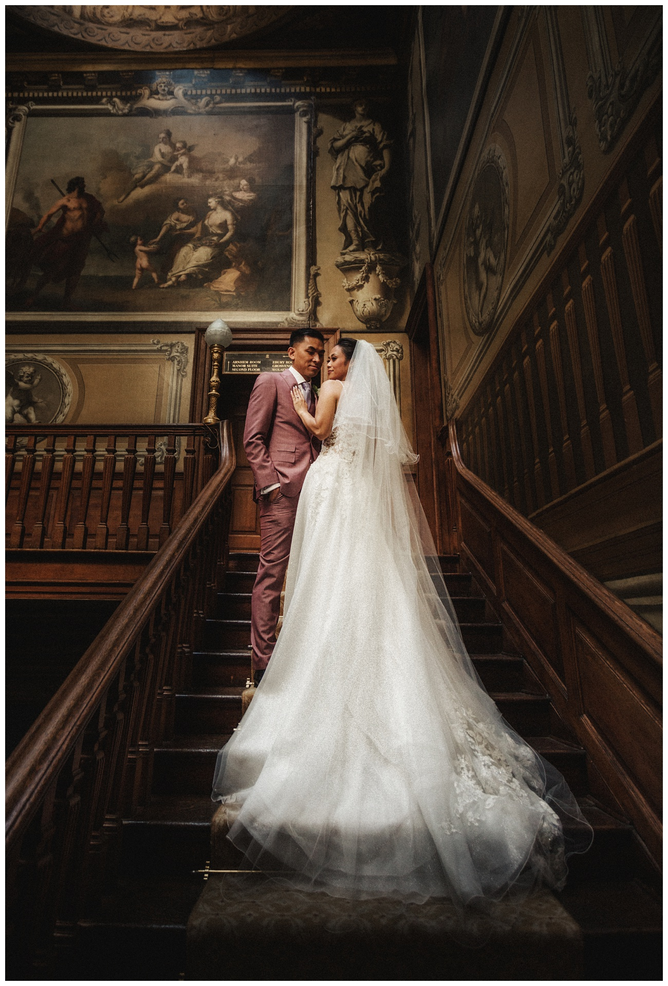 Bride and groom pose on the stairs inside Moor Park Mansion