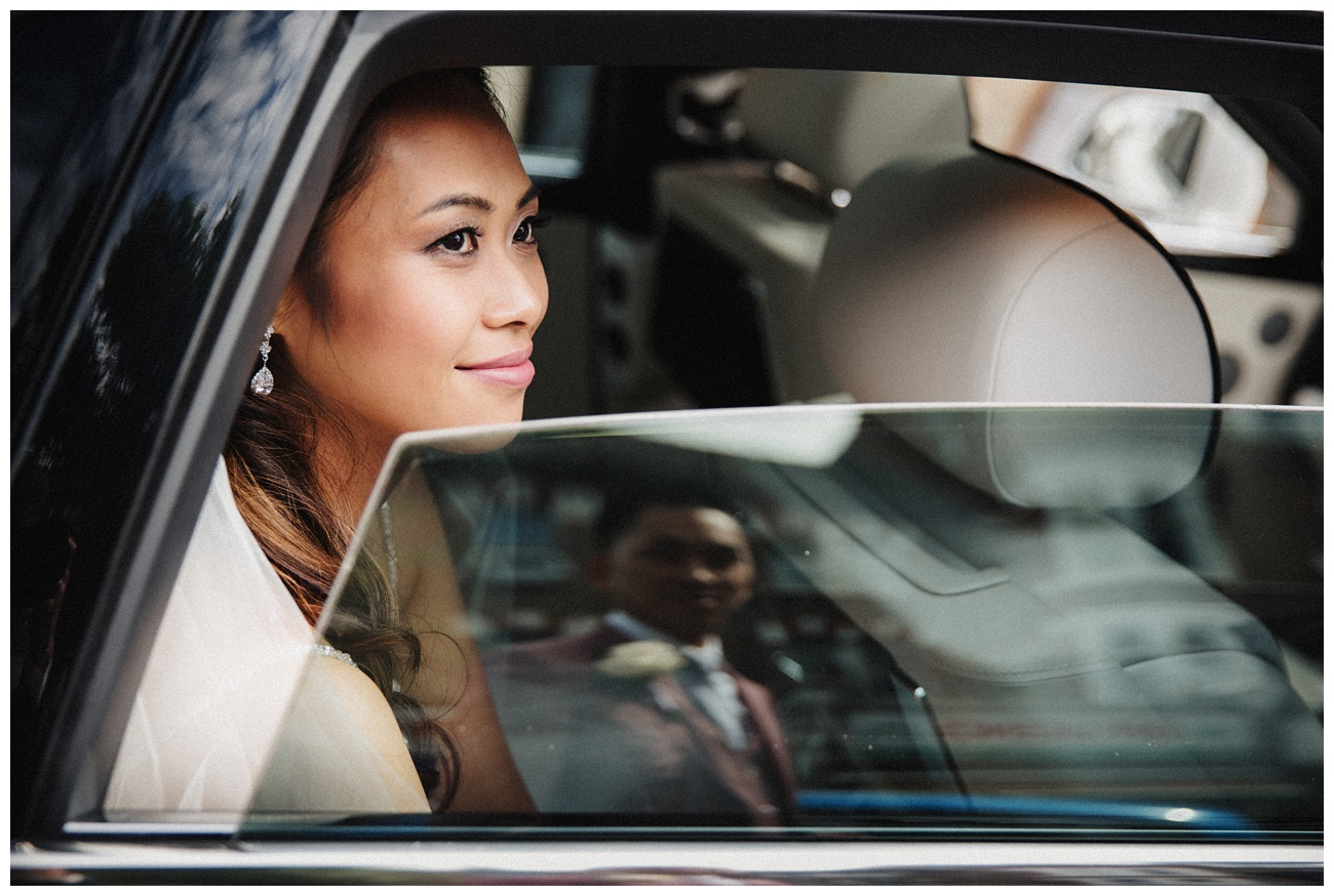 The bride looks out of the car window as the groom waits to open the door for her