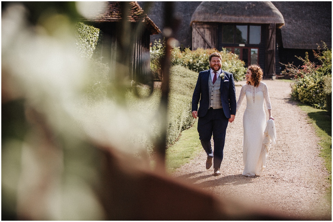 Bride and groom walk holding hands along a gravel path in the sunshine
