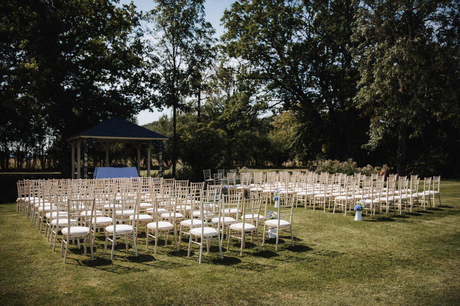 Colville Hall outdoor wedding setting. Chairs lined in front of the wooden Pagoda.