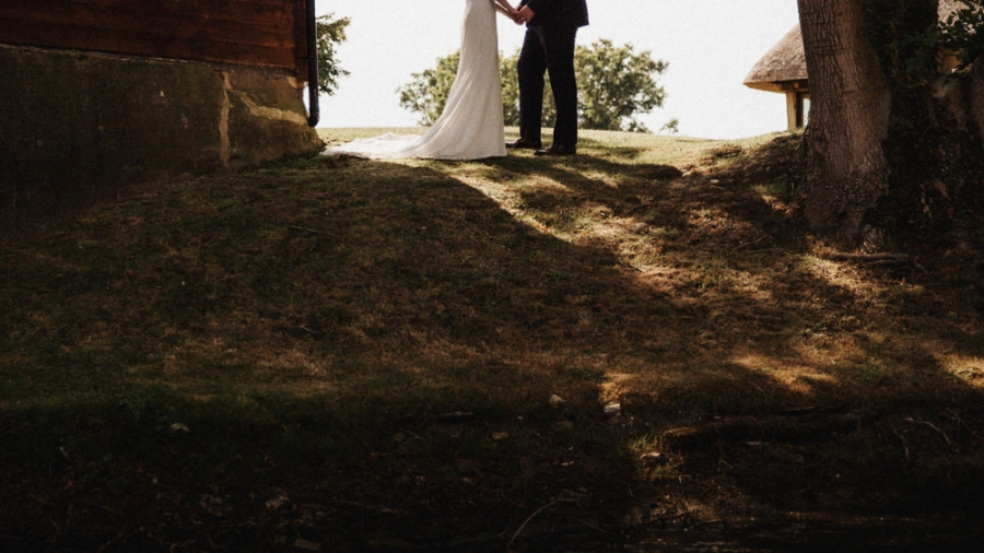 Bride and groom holding hands on a hill near a lake