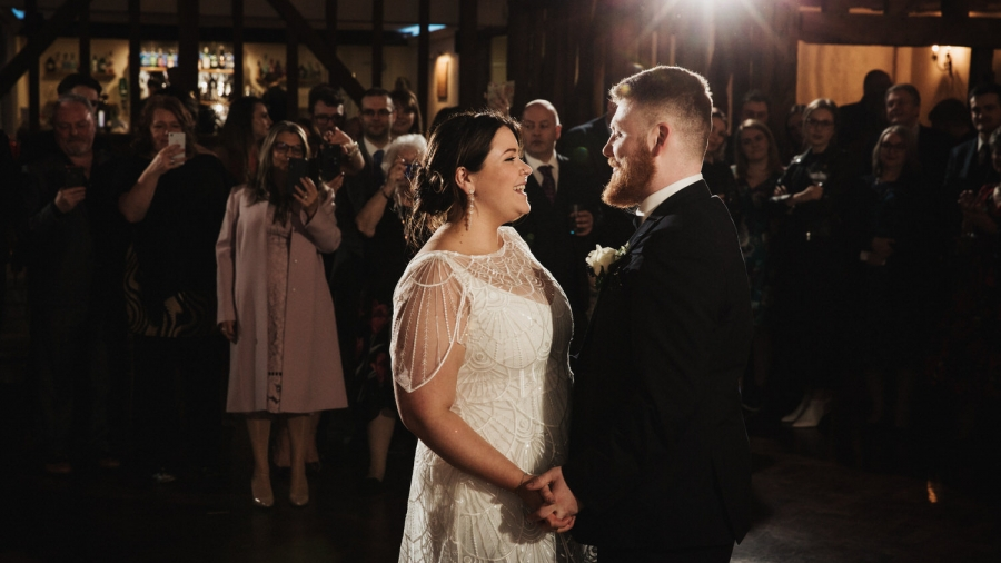 The bride and groom smile during their first dance