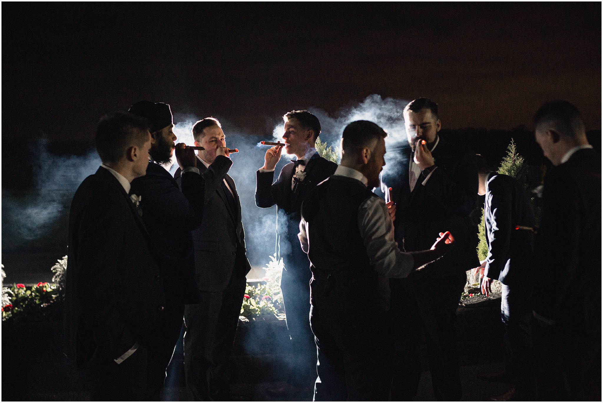 The groomsmen smoke cigars outside in the evening