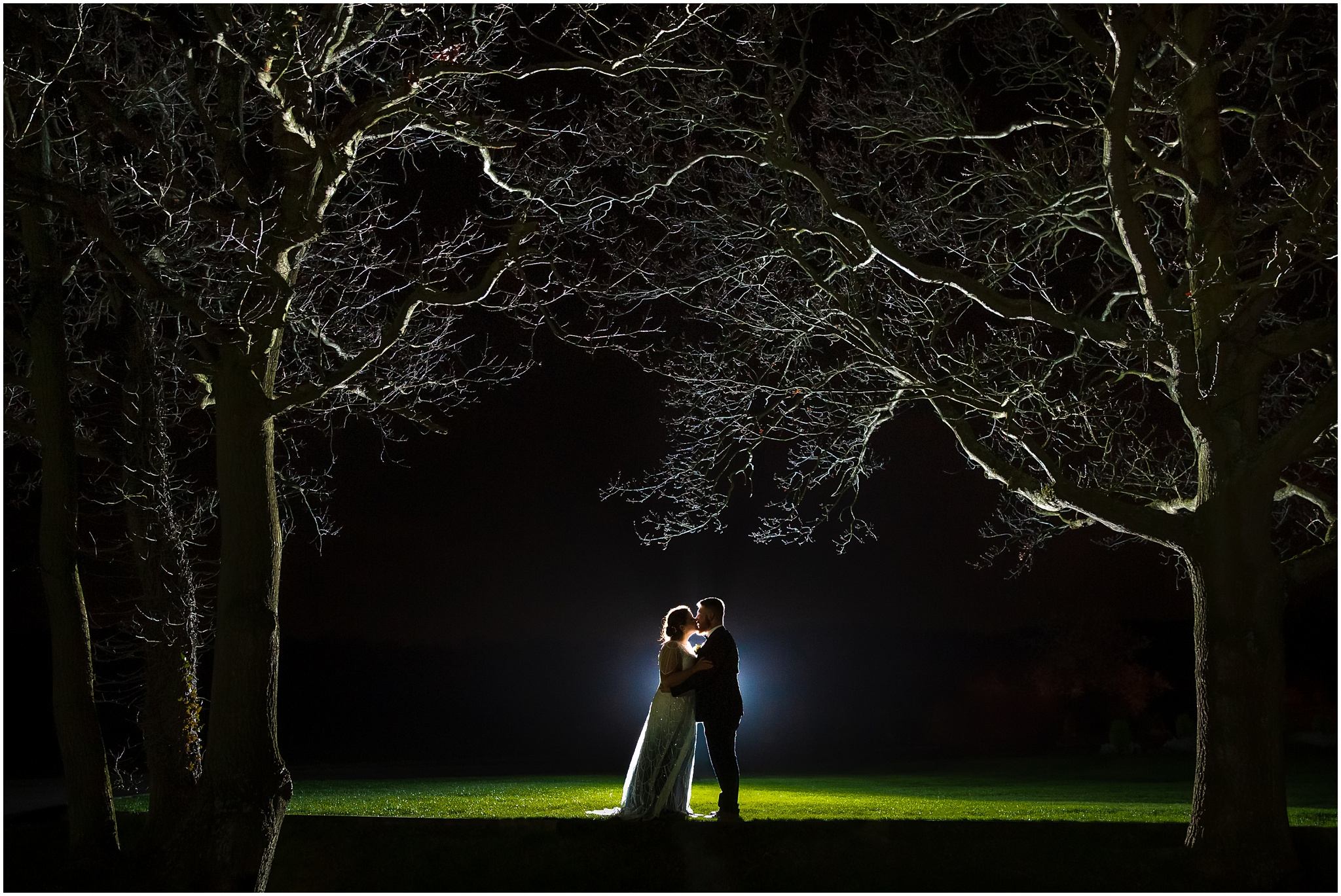 The bride and groom kiss during an evening shot next to 2 trees
