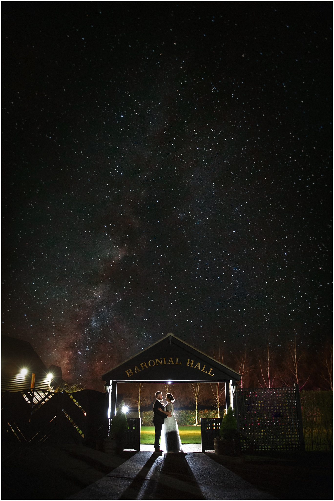 The bride and groom hold each other under a sign at Crondon Park with the stars in the sky.