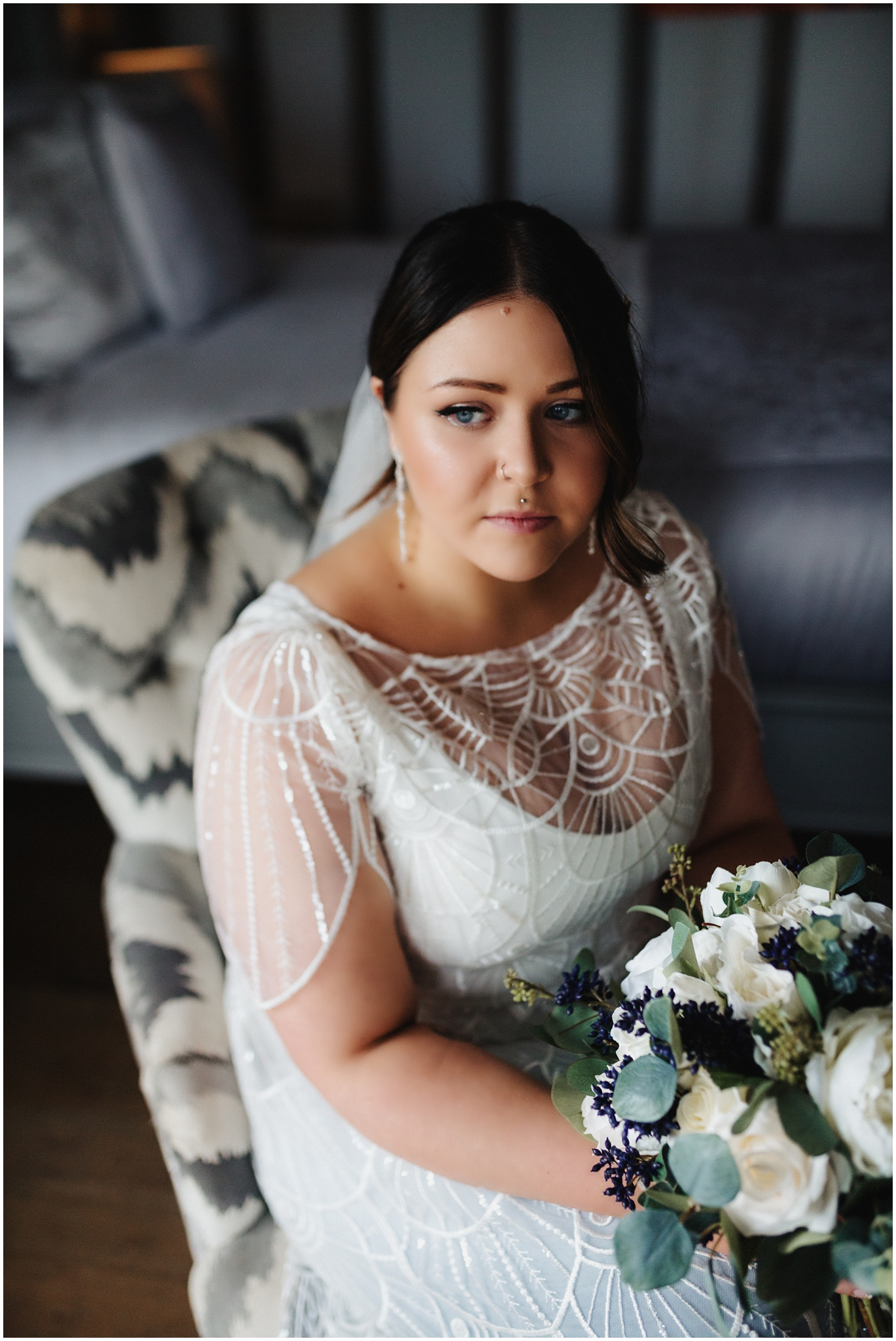 A portrait of the bride sitting down with her wedding flowers