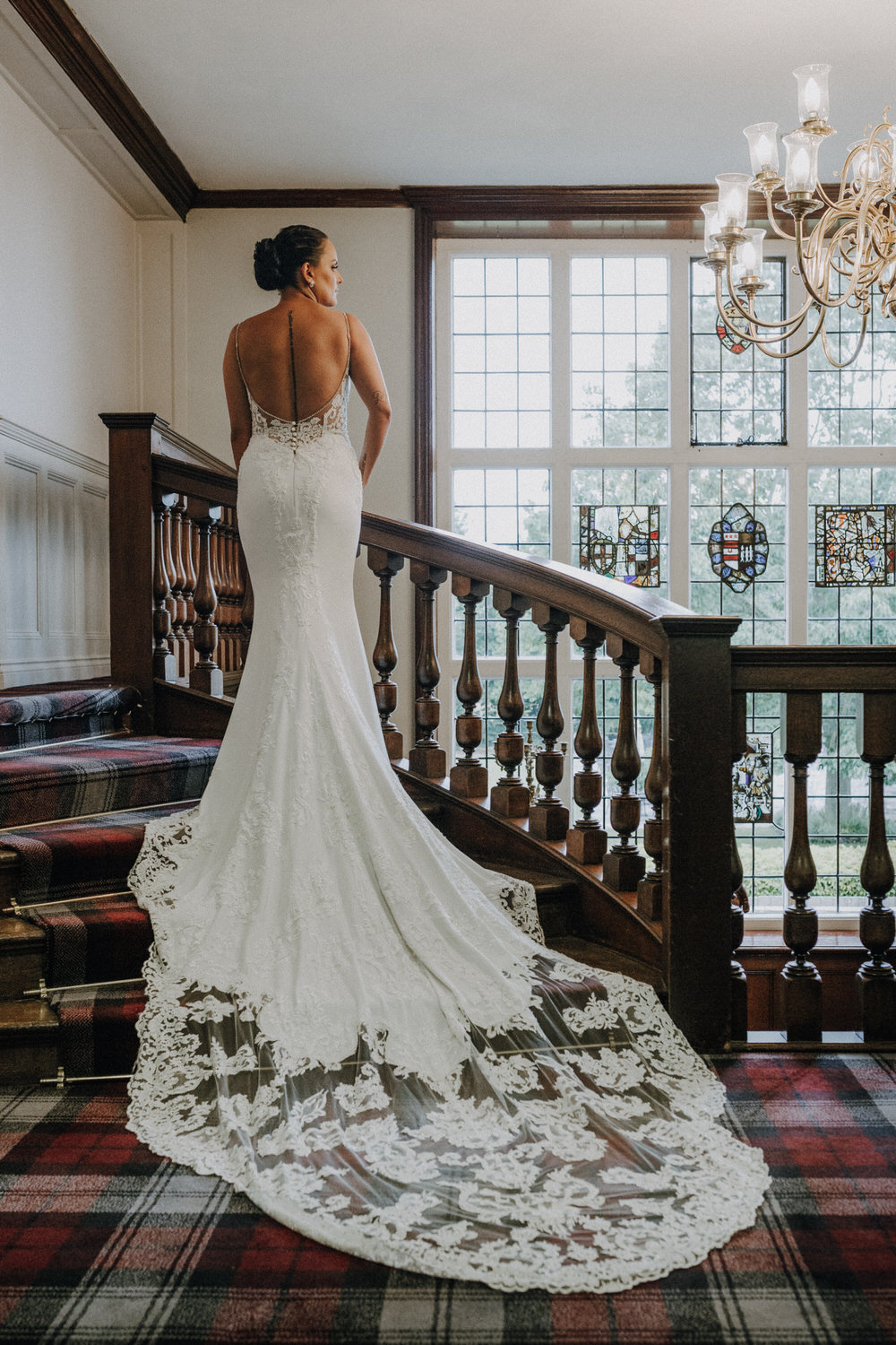 A bride stands on the stairs and poses in her wedding dress