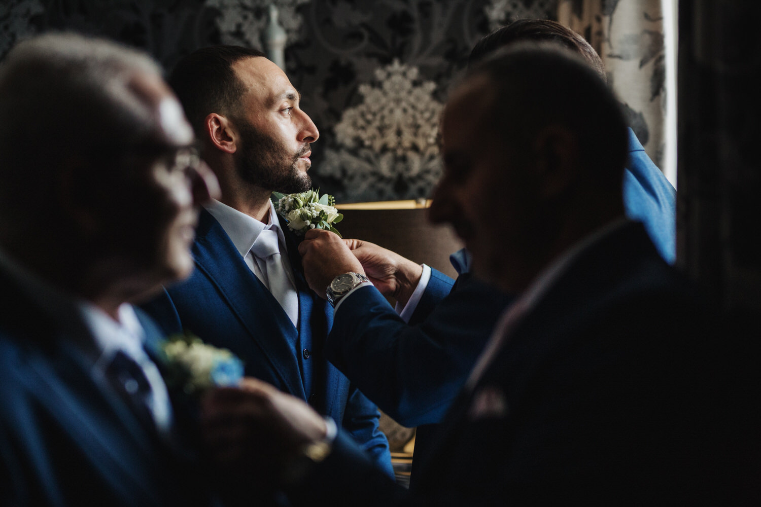 a groomsmen helps the groom with his button hole