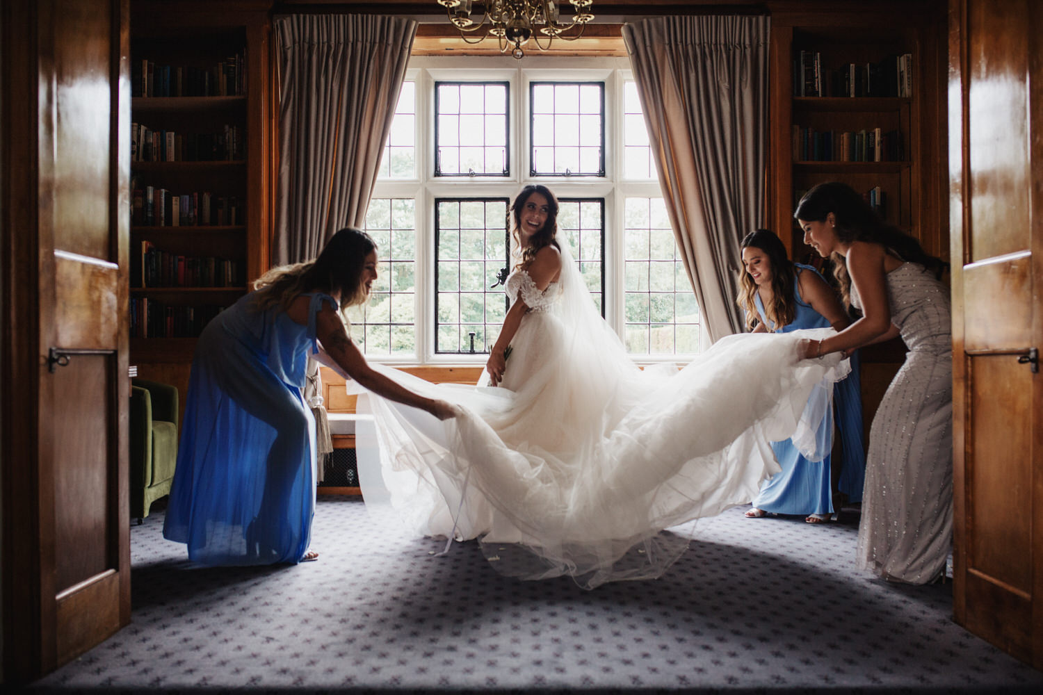 the happy bridesmaids help the smiling bride with her wedding dress