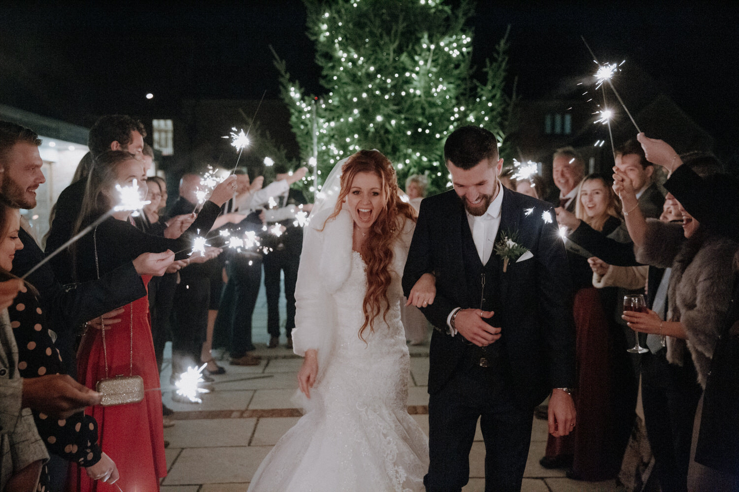 Bride and groom walk through sparklers held by their wedding guests at night