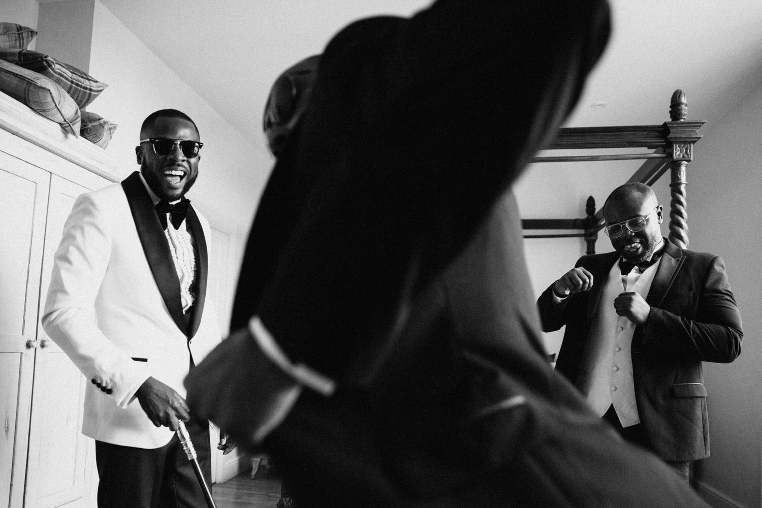 The groomsmen laugh and dance in their hotel room