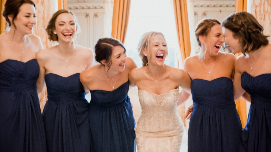 bride and bridesmaids hug and laugh together in the bridal suite
