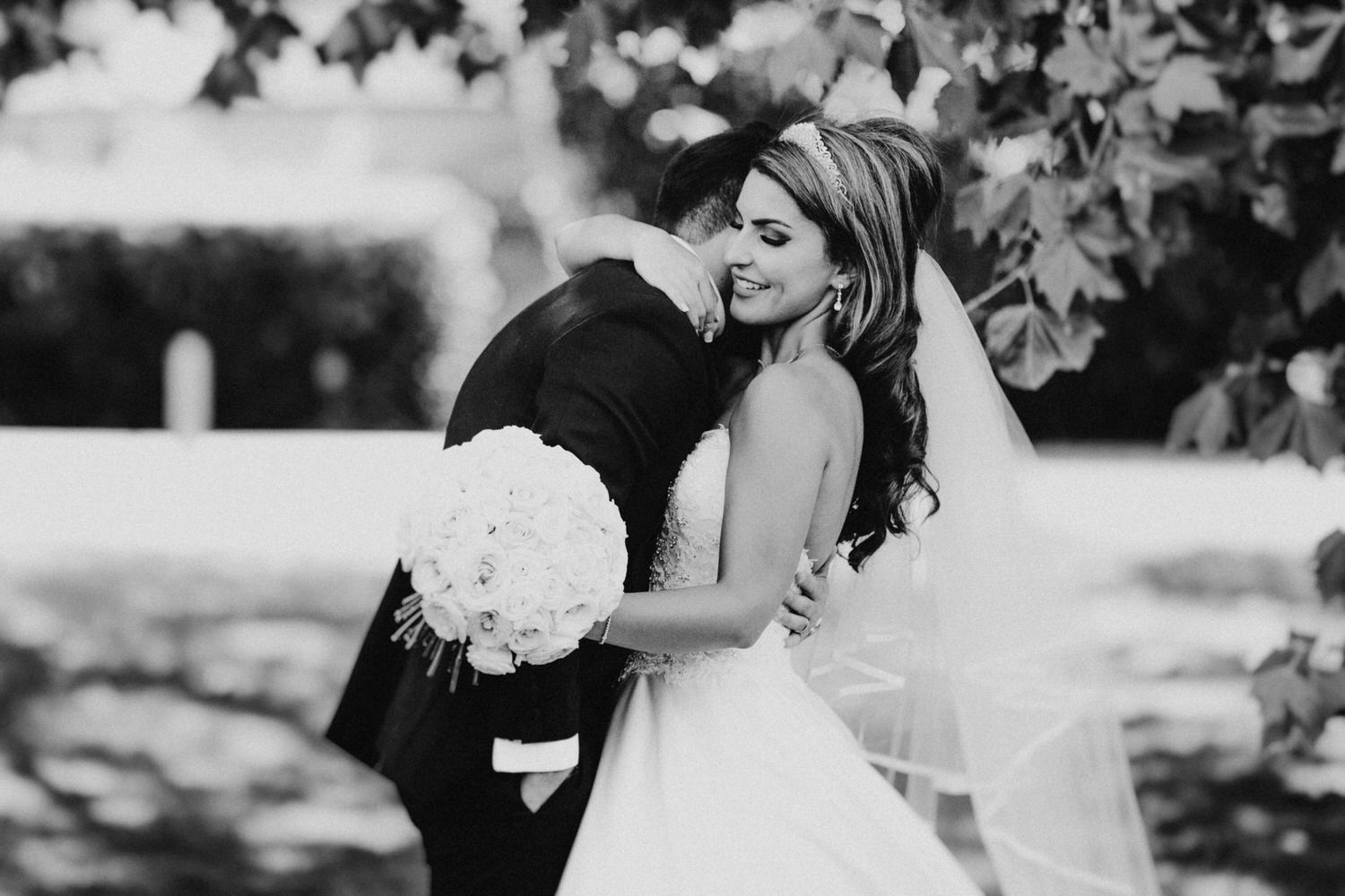 A happy bride and groom hug under a tree