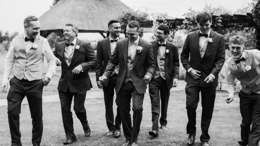A black and white image of the groomsmen laughing together