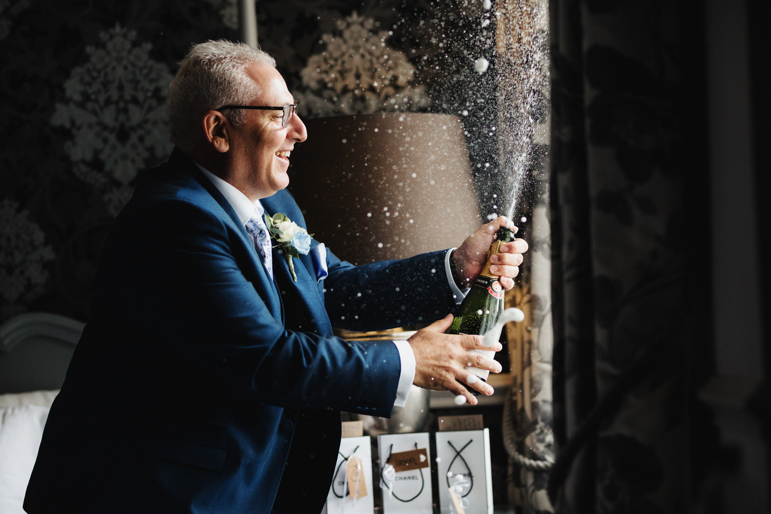 A groomsman opens a champagne bottle in the hotel room and it sprays everywhere