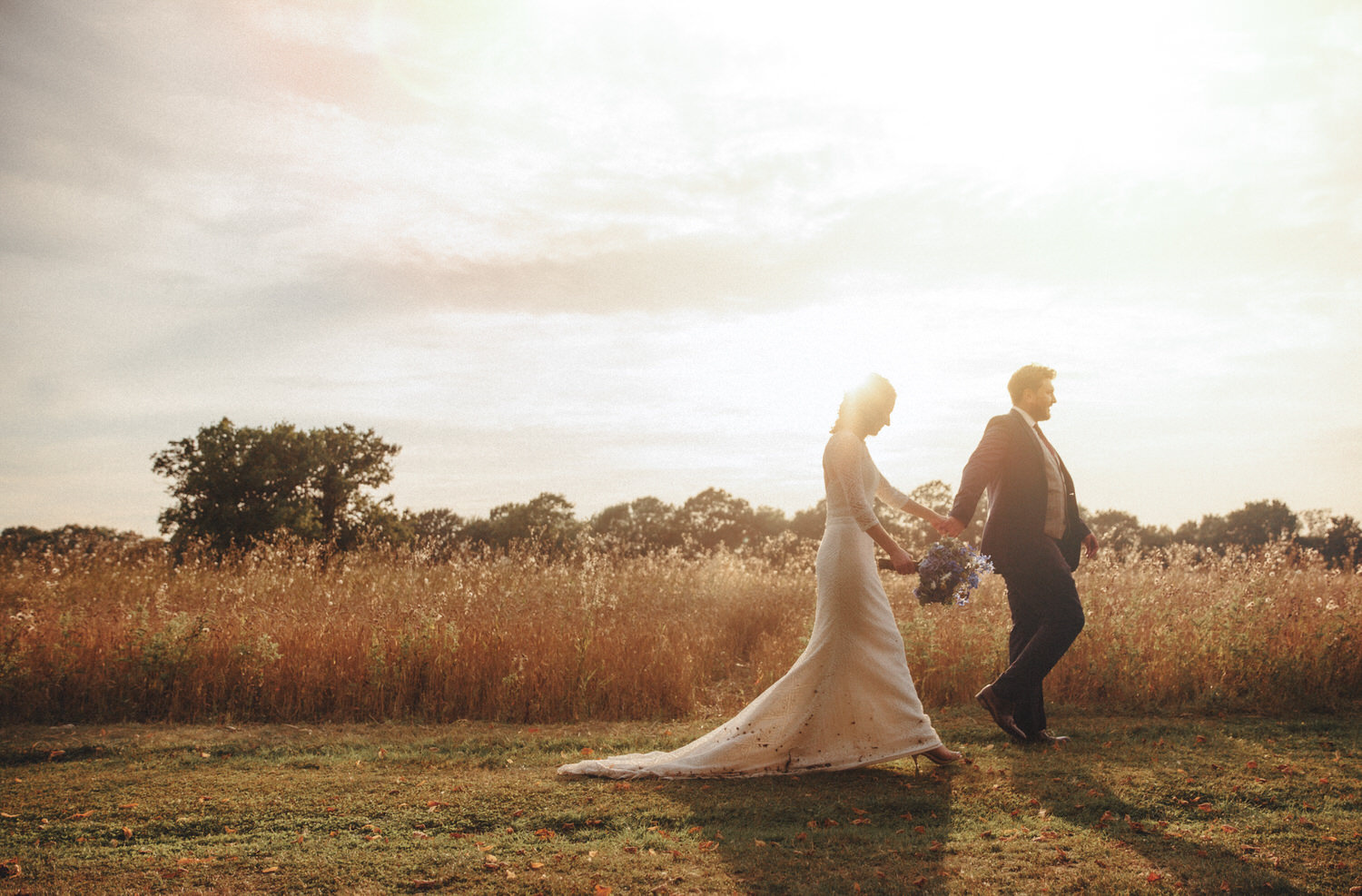 Bride and groom walk in a field during sunset