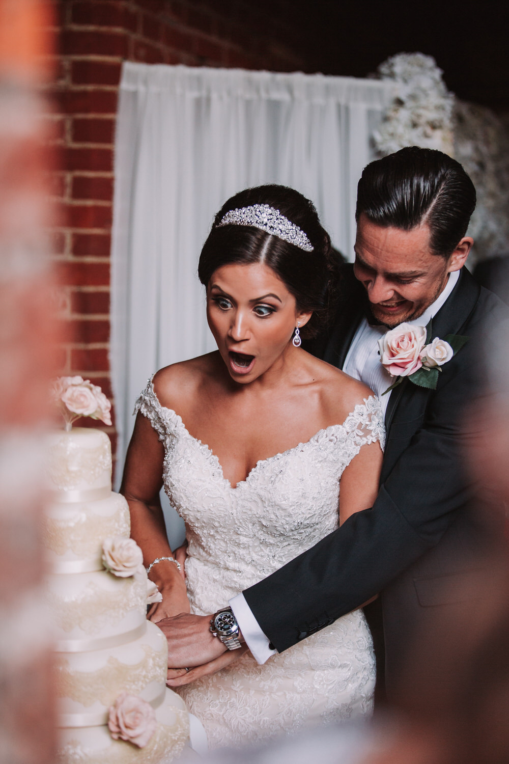 A surprised bride cuts the cake with her husband