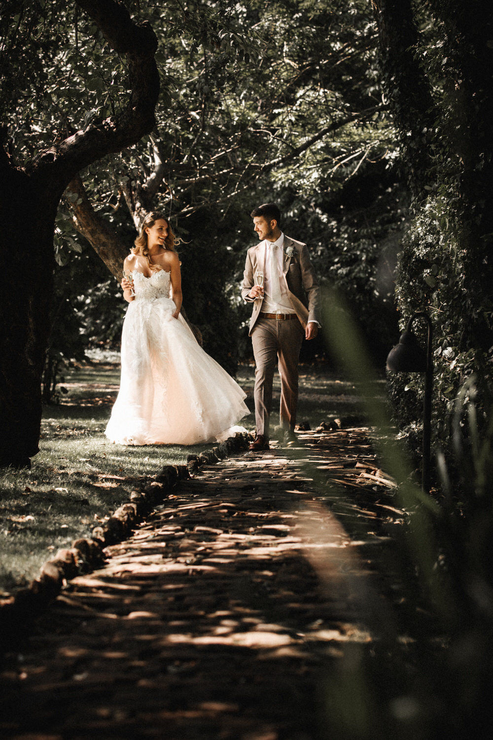 The bride and groom take a country walk together while drinking champagne