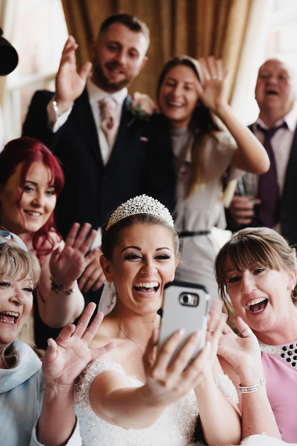 A wedding party laughs and reacts to a relative on the phone during the wedding