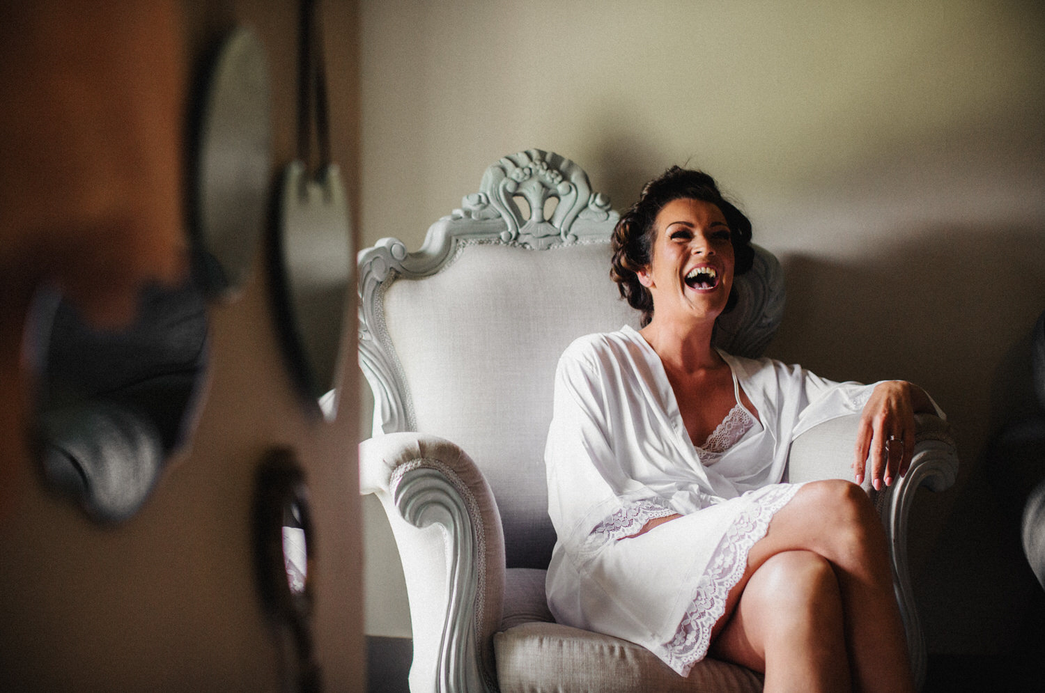 A bride laughs while sitting in her dressing gown