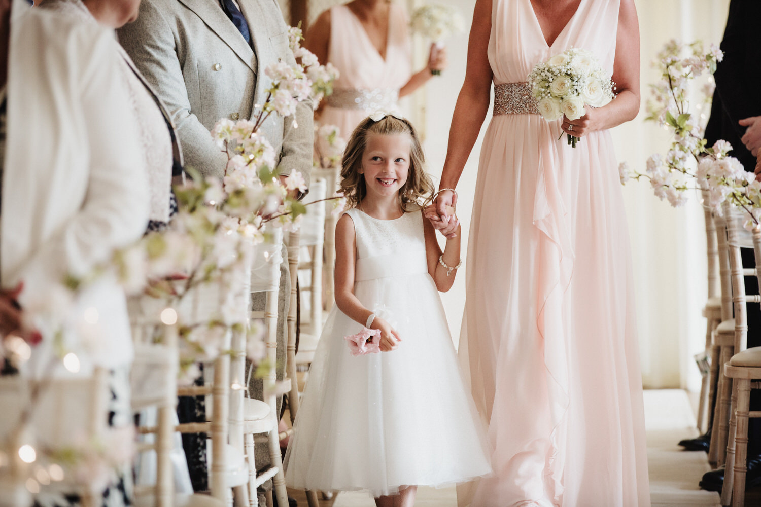 A happy flower girl walks down the aisle during the ceremony