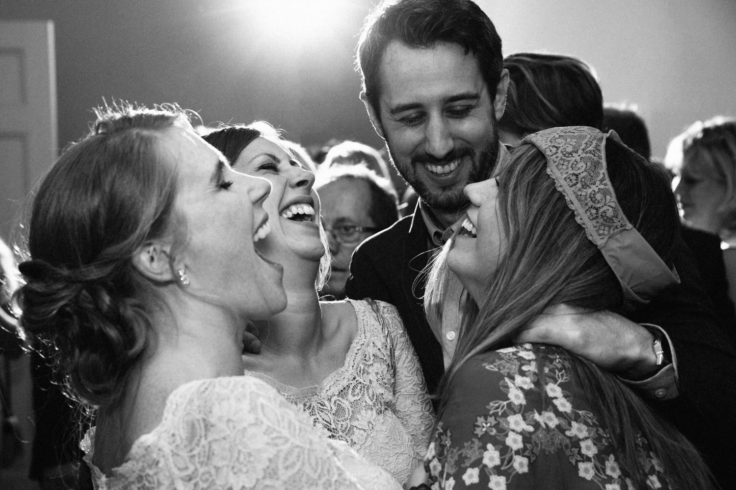 wedding guests laugh on the dance floor in this black and white image