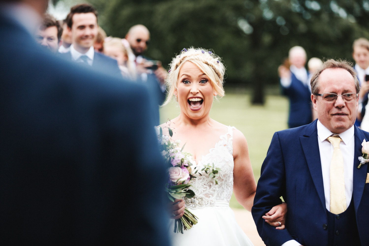 The brides reaction to her partner as she walks down the aisle with her dad