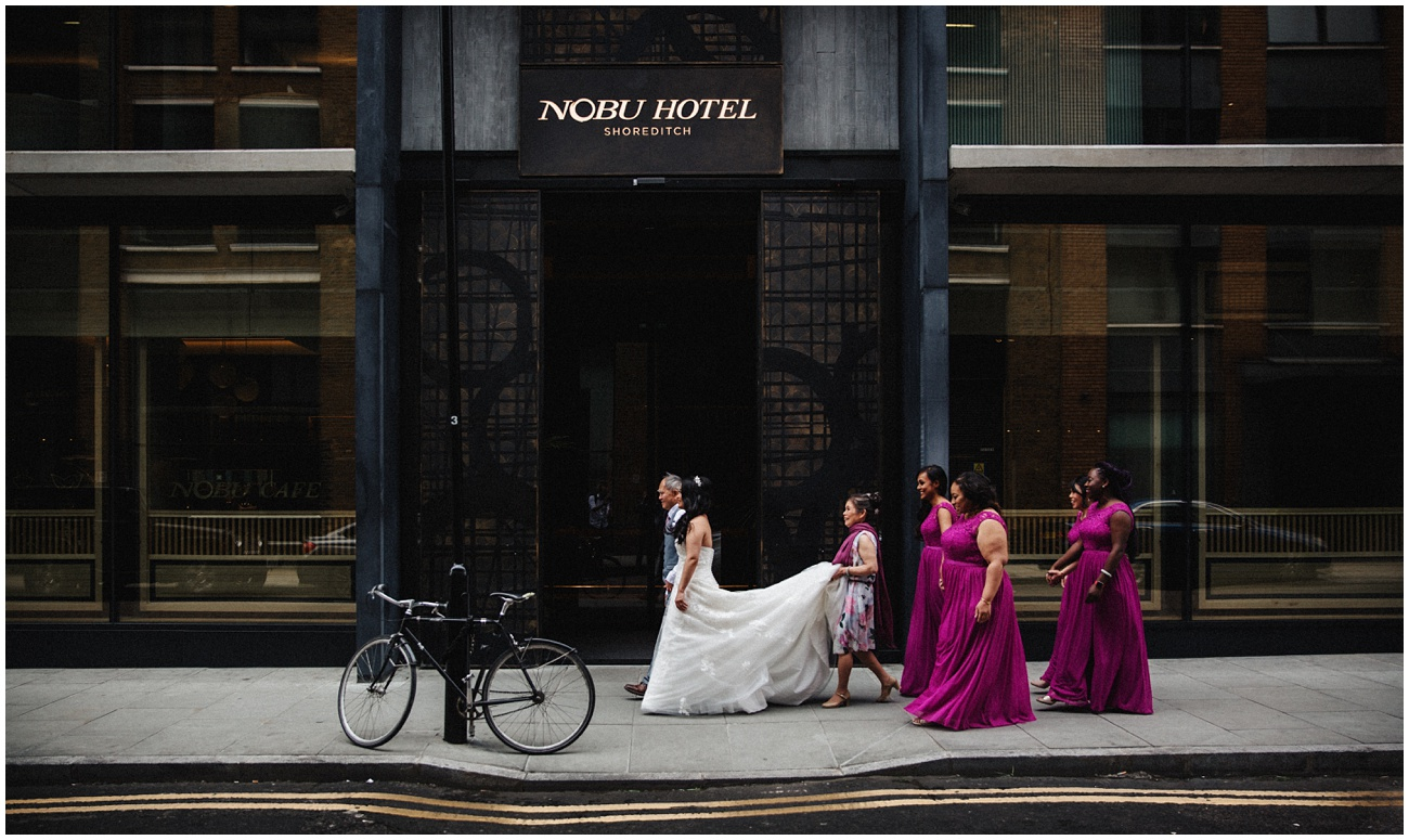 The bride waits outside Nobu hotel with her parents and bridal party for a  taxi