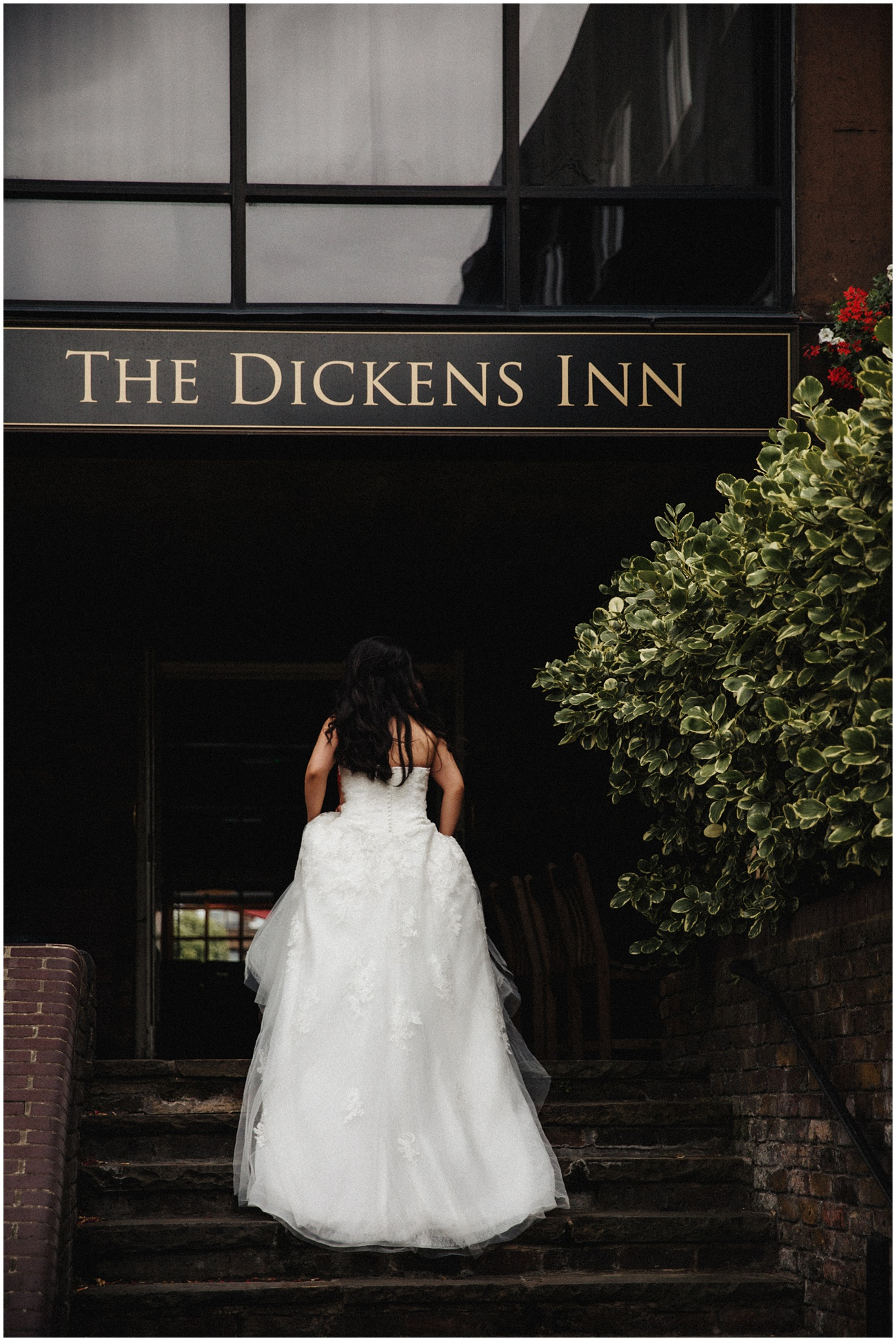 The bride in her wedding dress walking up the stairs to the Dickens Inn