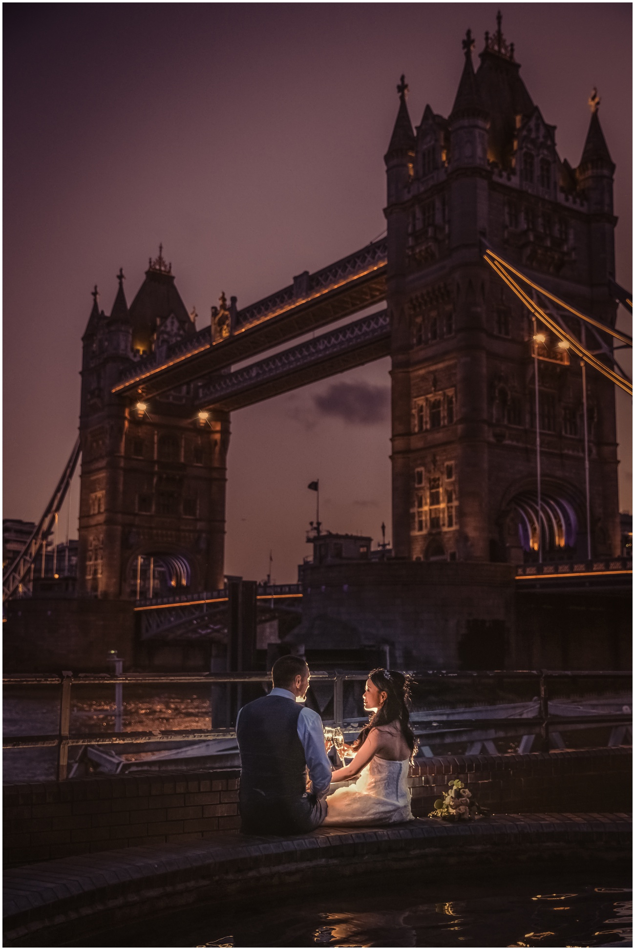 An evening portrait of the couple sitting drinking champagne next to the Tower Bridge