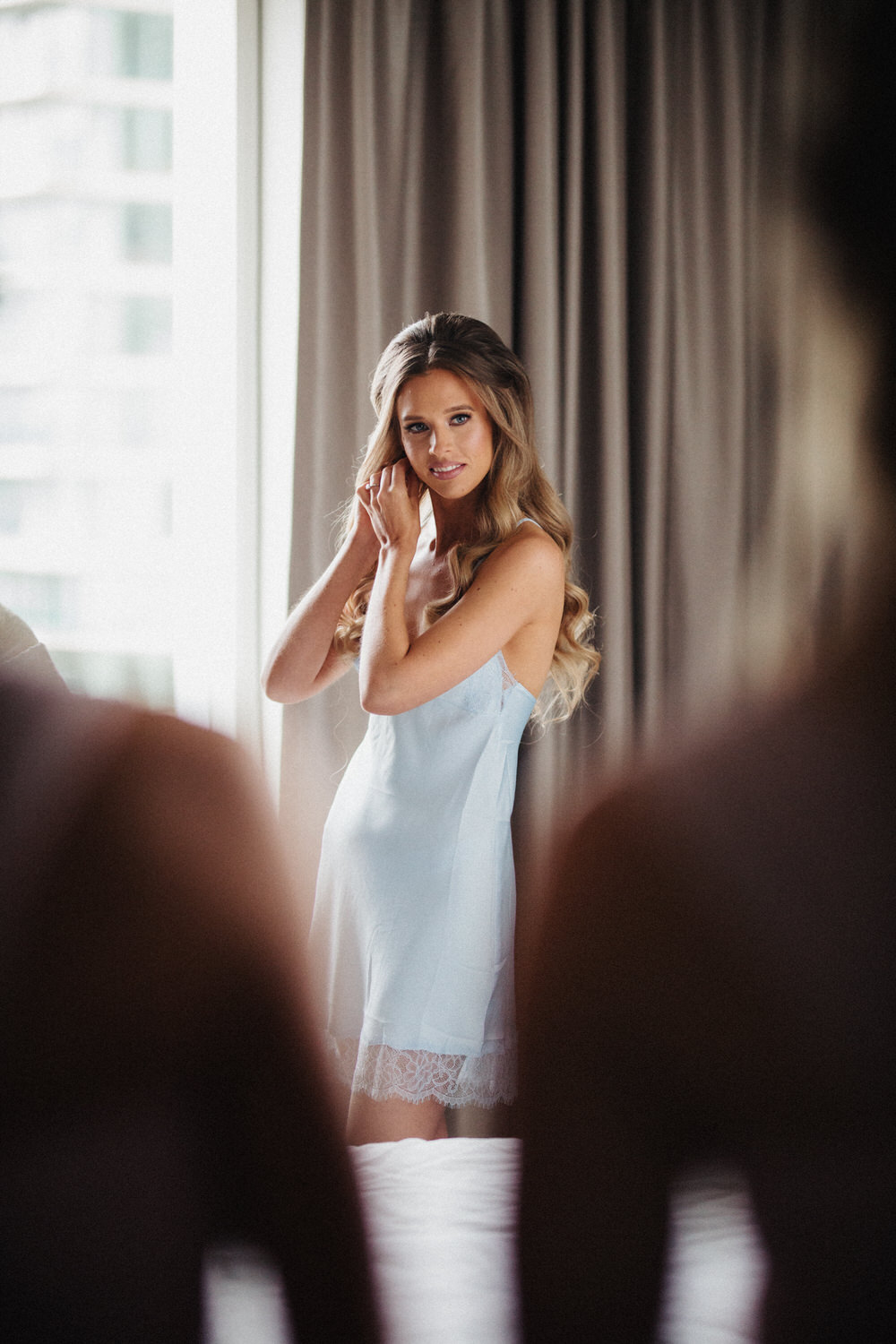 a bride puts her earrings in while getting ready in her hotel room