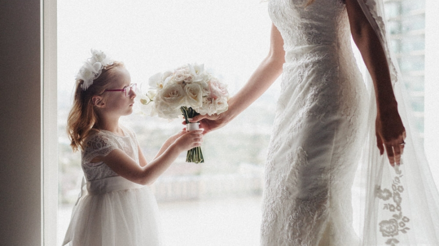 the bride gives the flower girl some flowers