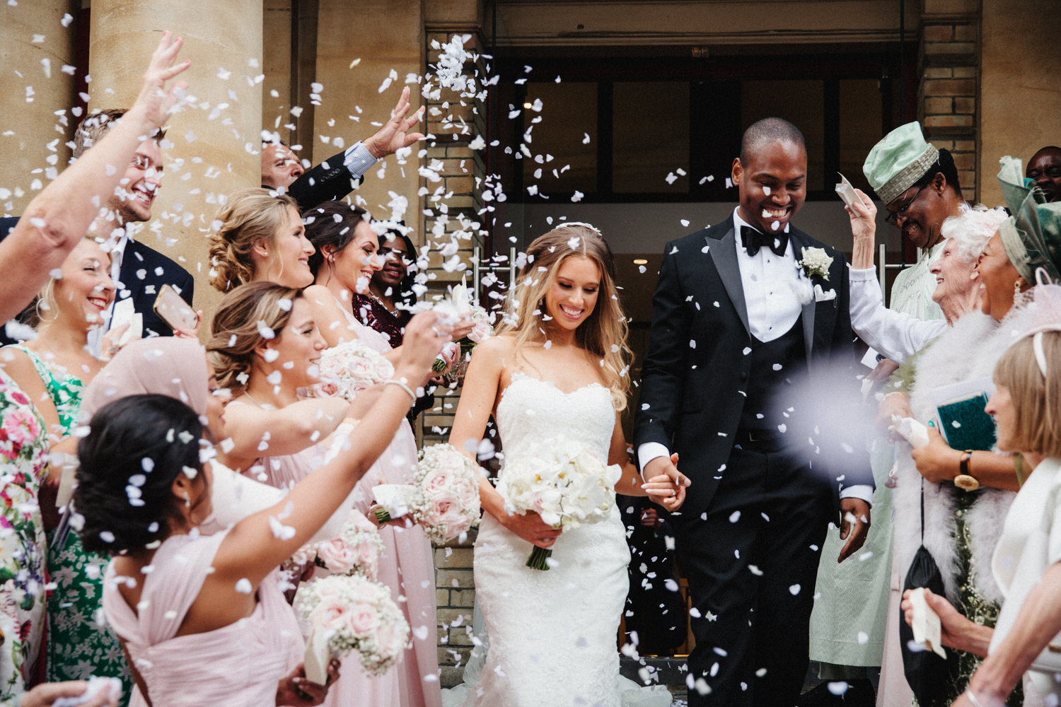 Bride and groom walk through confetti thrown by guests