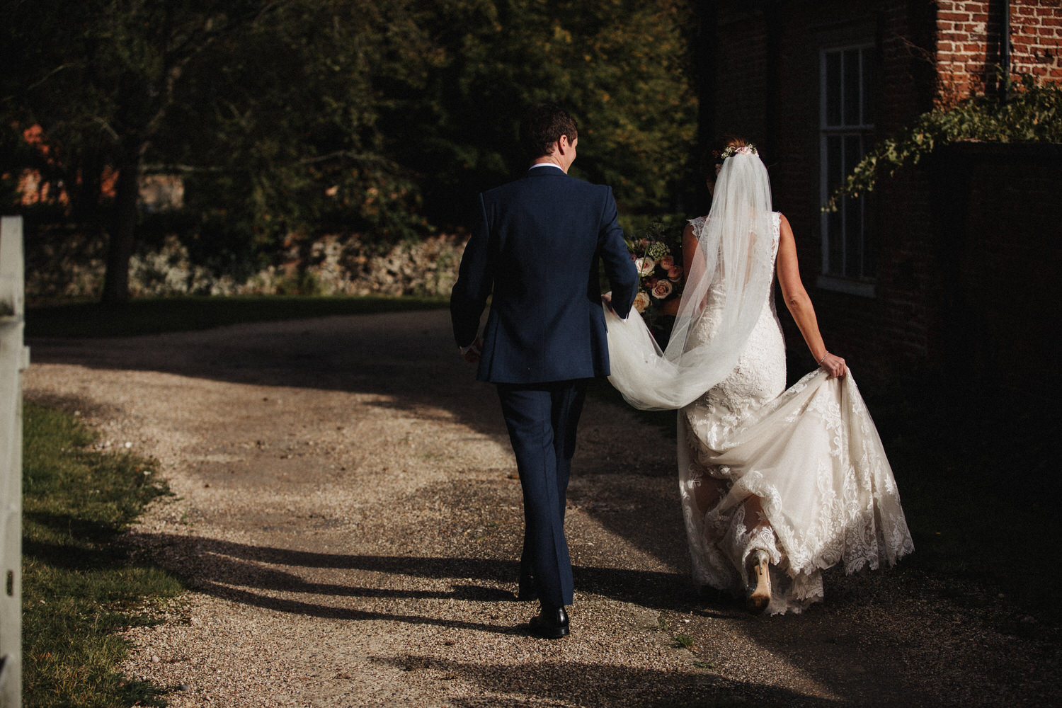 bride and groom walk down a path in the sunshine
