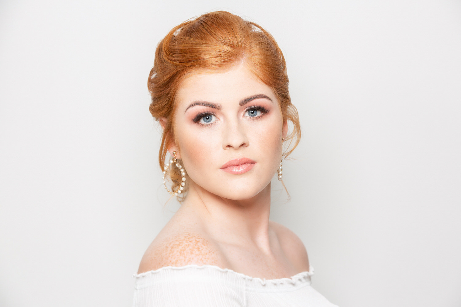 Front headshot of red haired bride looking at the camera and wearing earrings