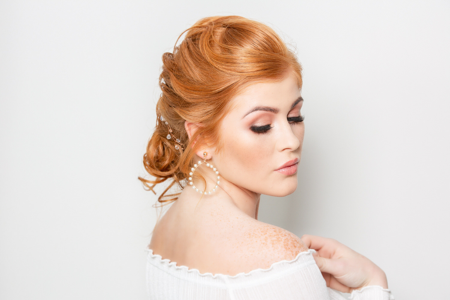 A red haired bride looking down towards the floor to show her makeup