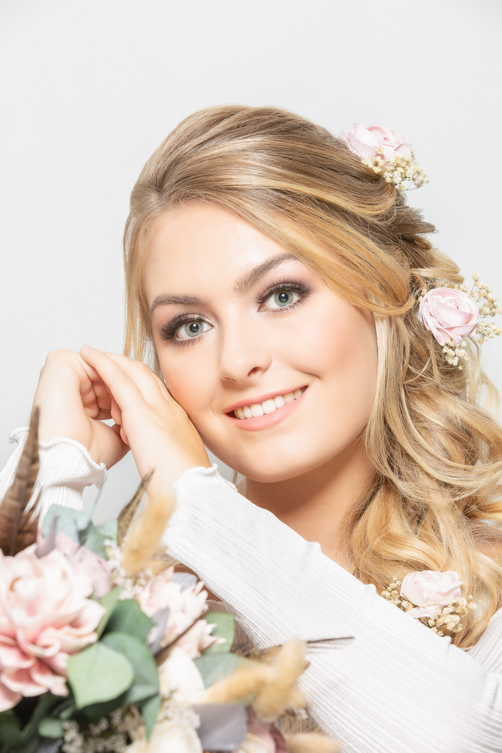 Portrait of a blonde haired bride sitting with her hair and makeup complete