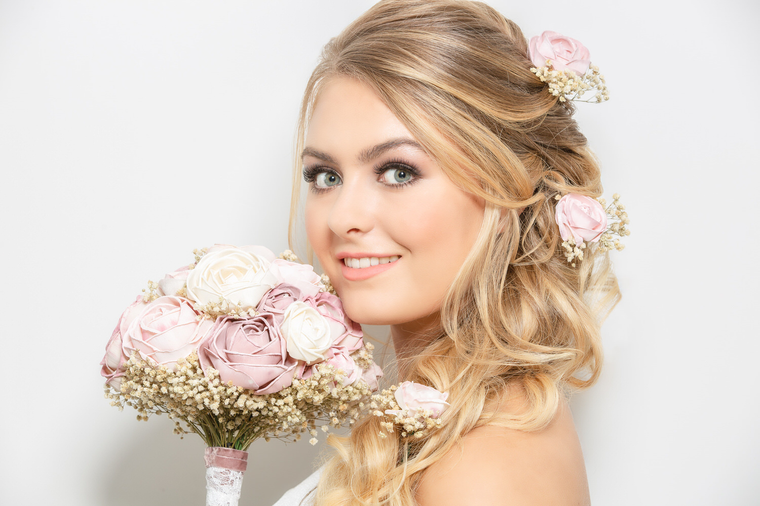 Side portrait of blonde bride holding a wedding bouquet