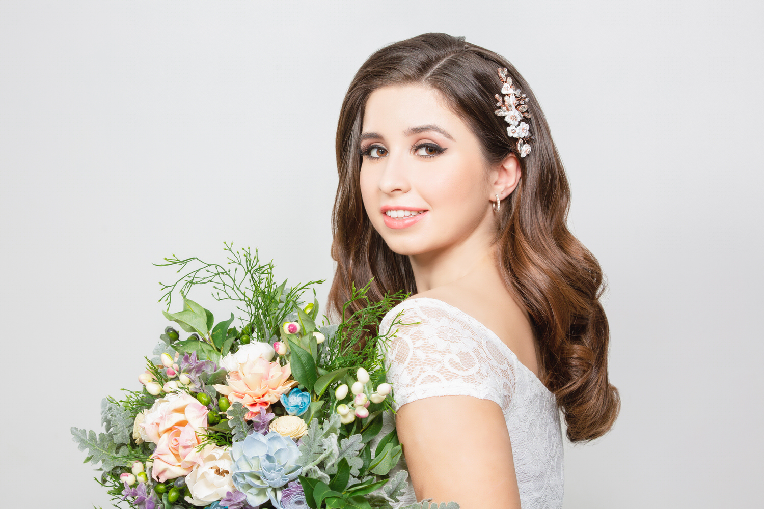 Brunette haired model holding flowers with white background