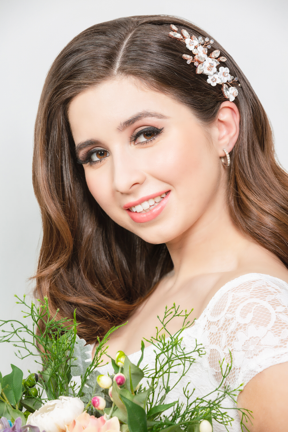 Brunette model with hair clip in her hair holding flowers