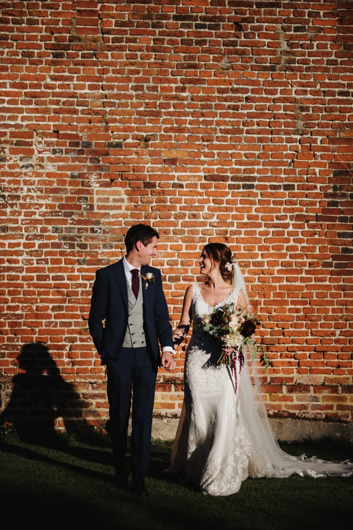 Bride and groom laugh in the sunshine next to the red brick wall
