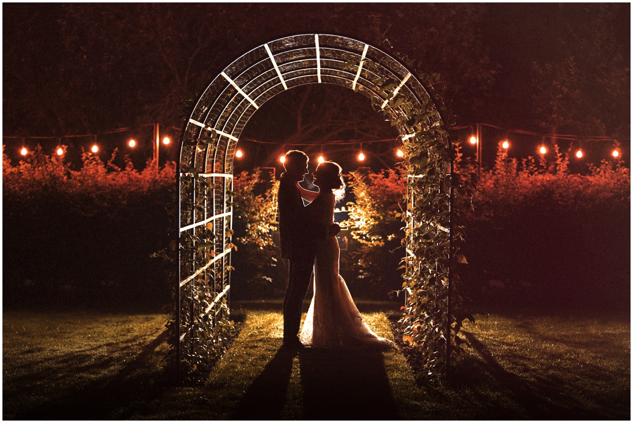 Bride and groom in a romantic photo with hanging lights in the grounds of the great lodge